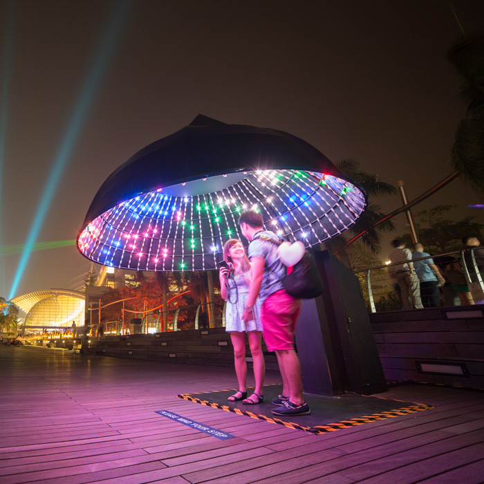 Travel photo by Singapore-based photographer Alexander Manton of a couple taking their own photo under a oversized, lit umbrella.