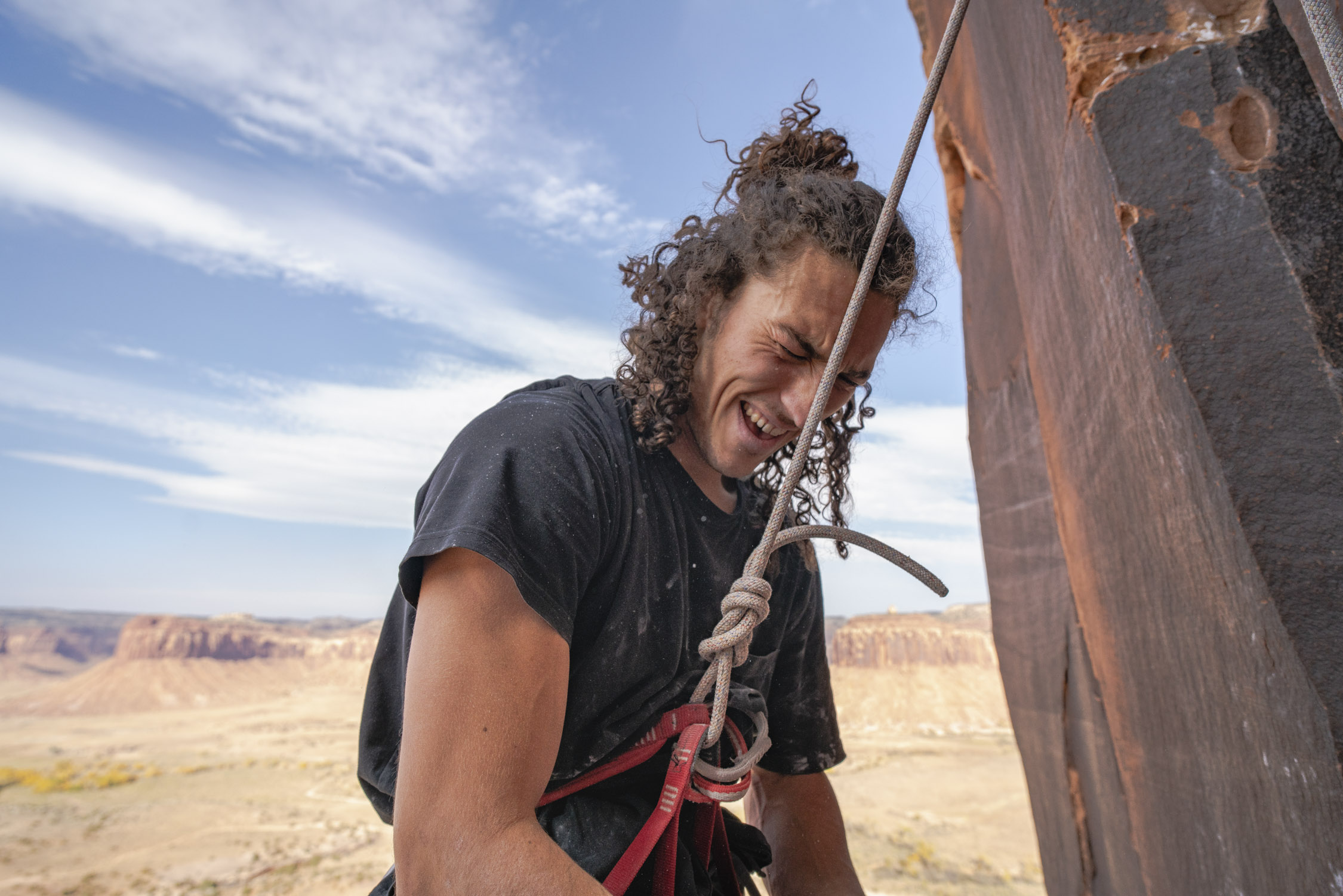 Dalton Johnson photographs laughing rock climber harnessed for Gregory Packs and Coalatree