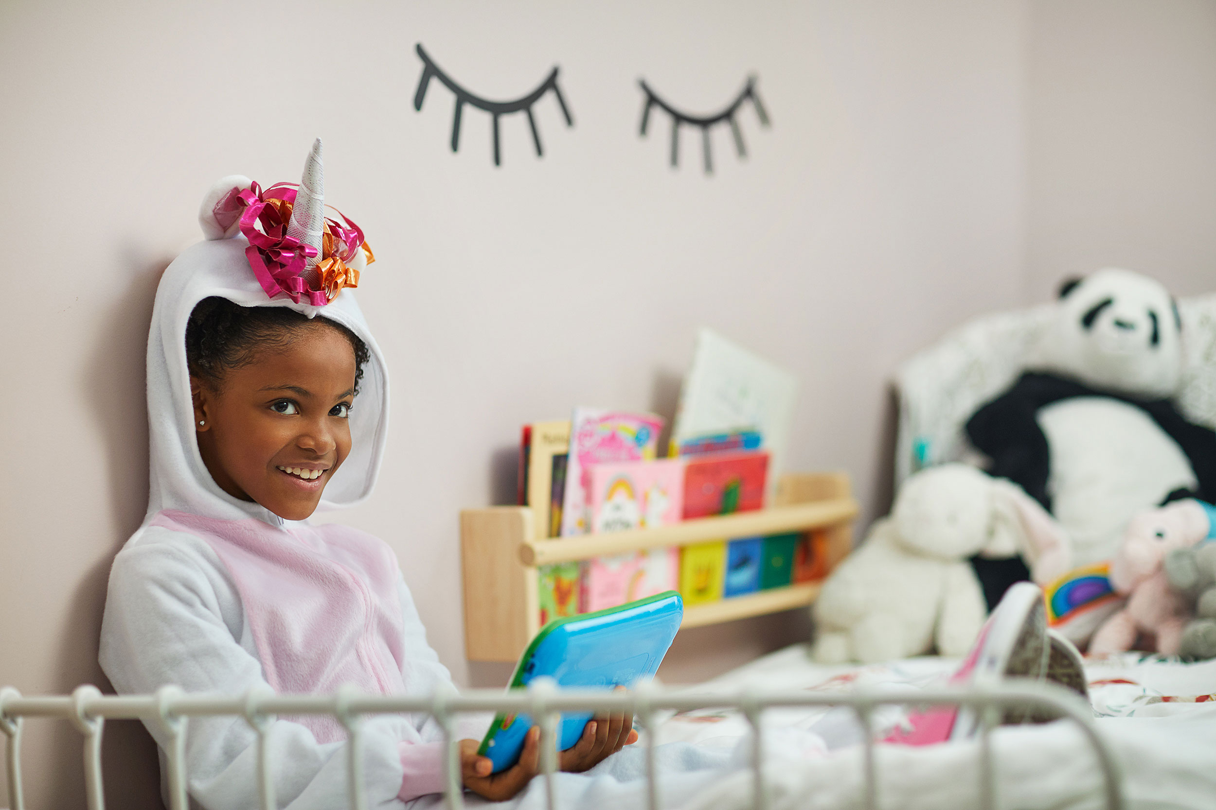 Natalia Weedy Calix a Black child dressed in a unicorn costume being pacified by an iPad