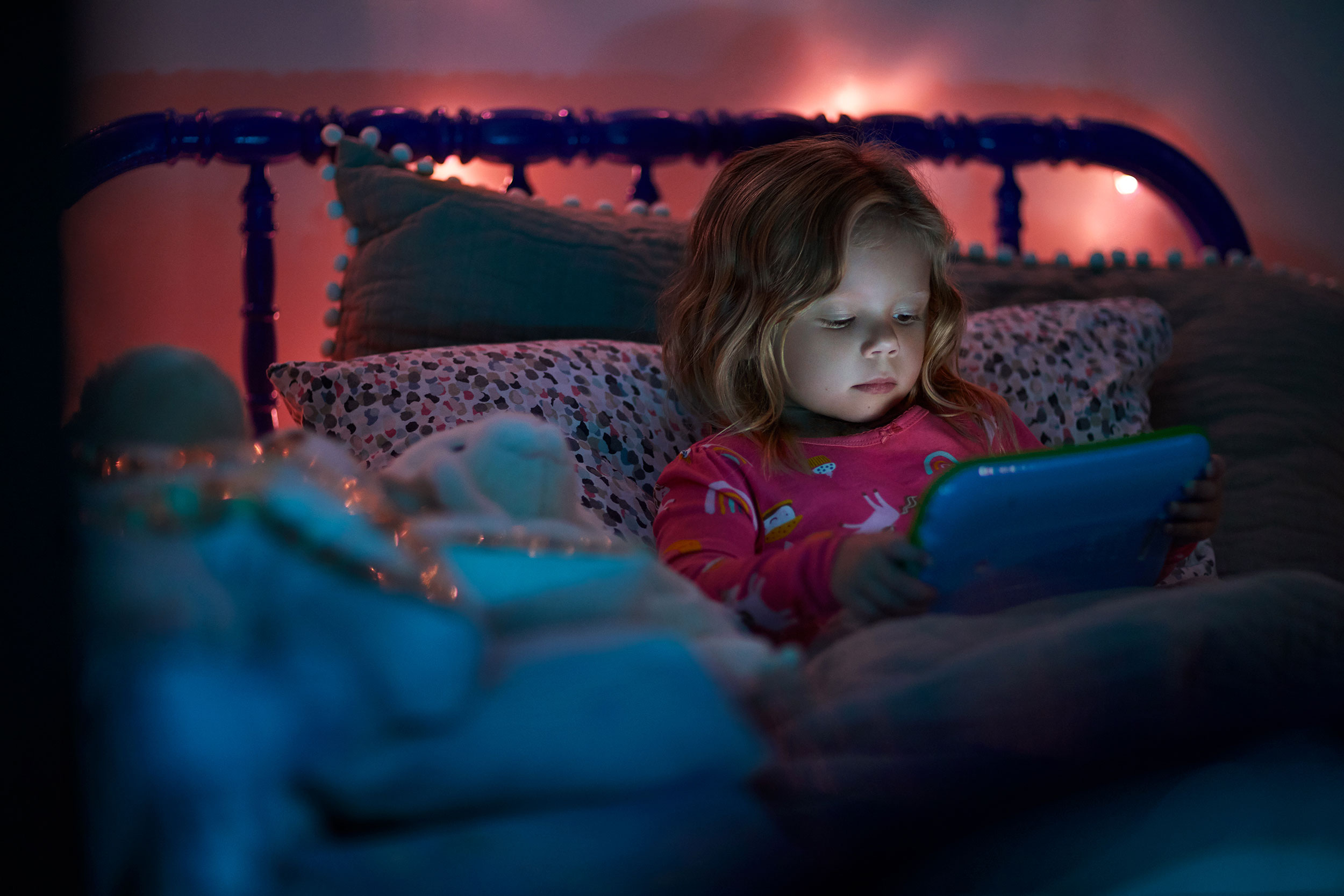 Natalia Weedy Calix a young White child in bed at night using a device rather than sleeping