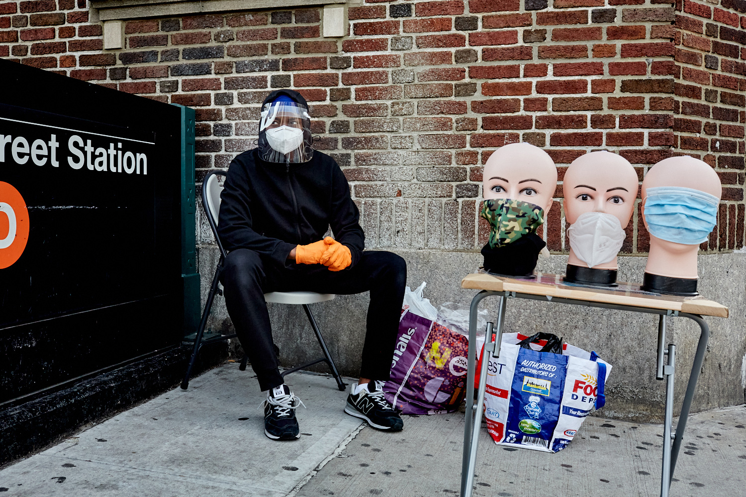 Man selling masks, sitting masked and faceshielded outside a subway station, by Stephen Speranza