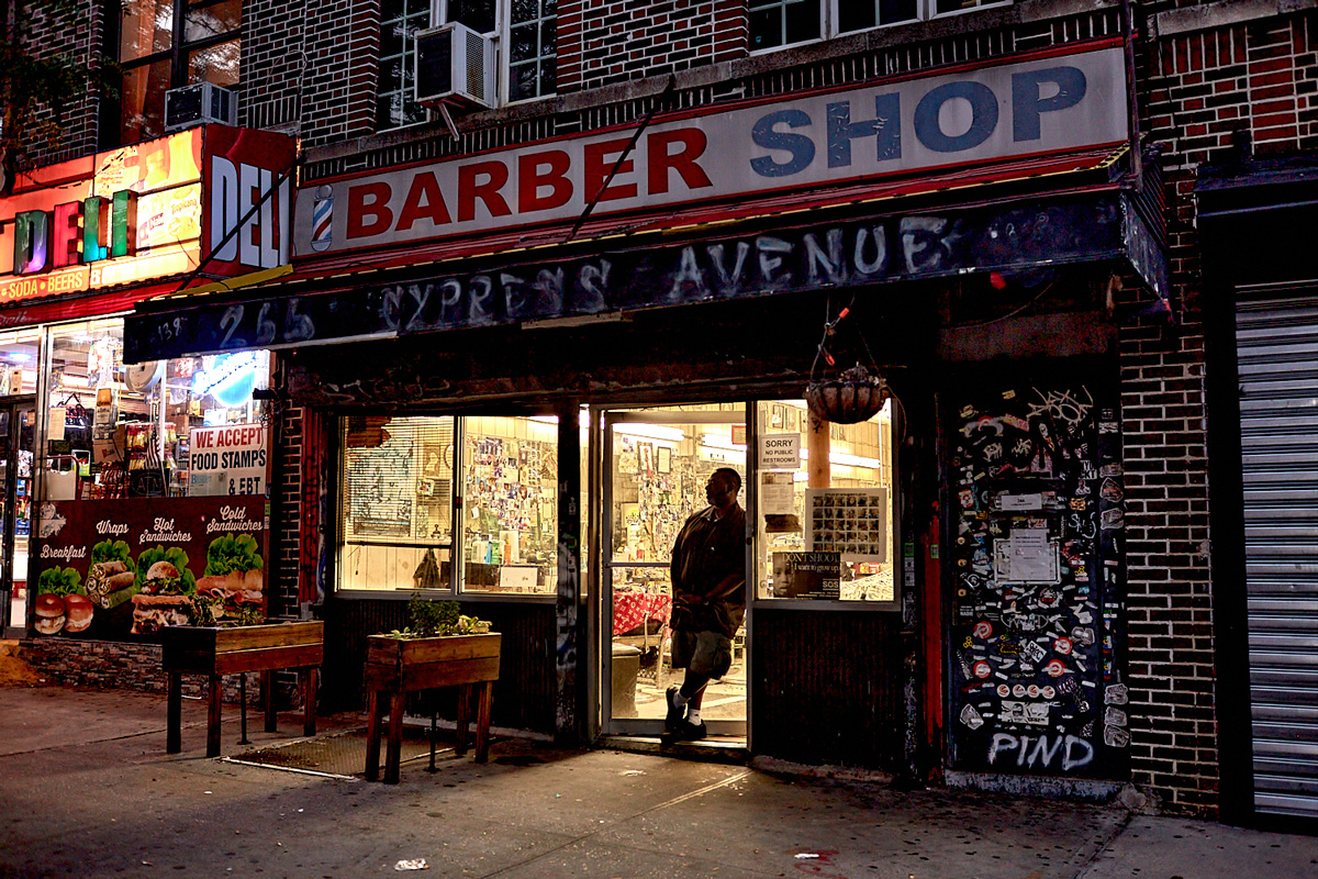 Dusk exterior of a barbershop with a man standing in the open doorway, by Stephen Speranza