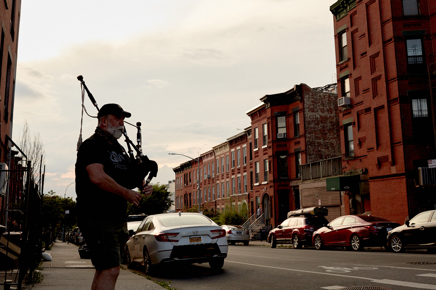 Lone bagpipe player on the sidewalk of a New York street, by Stephen Speranza
